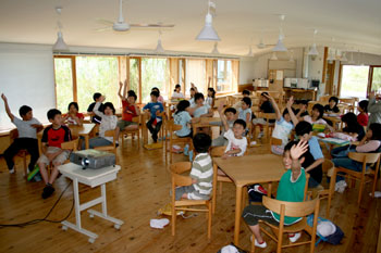 カフェテリアにて、太陽エネルギーや環境に関するクイズに元気よく手を挙げる子どもたち。
