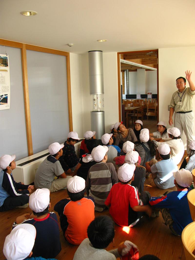 写真:集熱空気が通るダクトを前に説明をうける児童たち