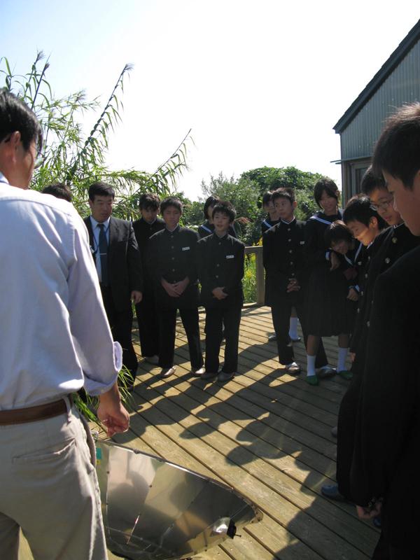 写真:ソーラークッカーの説明を聞く生徒たち
